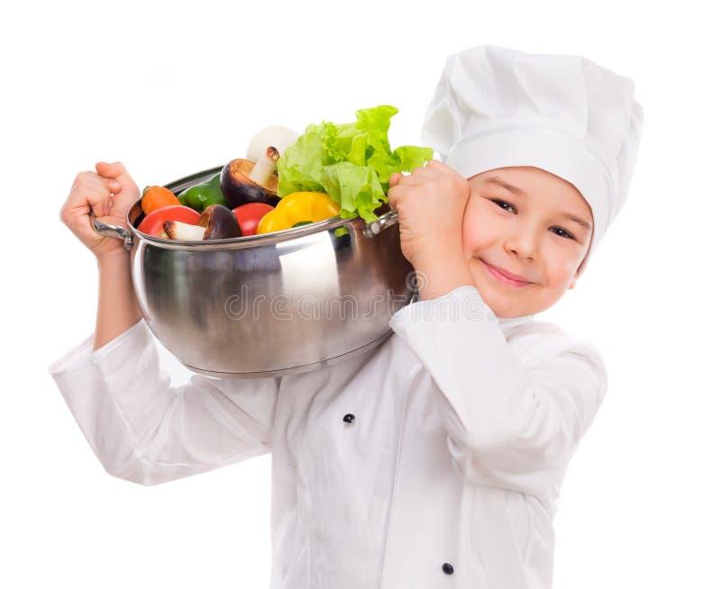 Μικρό παιδί στο άσπρο ομοιόμορφο τηγάνι εκμετάλλευσης στον ώμο στοκ φωτογραφία