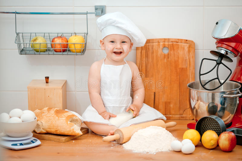 Μικρό παιδί στο κοστούμι μαγείρων στην κουζίνα με το ψωμί στοκ εικόνα