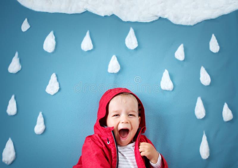 Μικρό παιδί στο μπλε υπόβαθρο στο παλτό με τις μορφές πτώσης στοκ φωτογραφίες με δικαίωμα ελεύθερης χρήσης