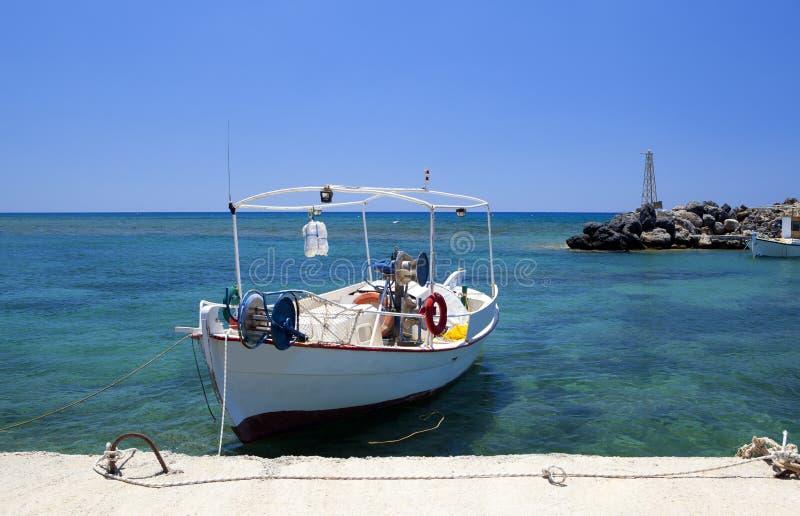 Μικρό παλαιό άσπρο αλιευτικό σκάφος στο λιμάνι, την μπλε θάλασσα και τον ουρανό στοκ φωτογραφίες