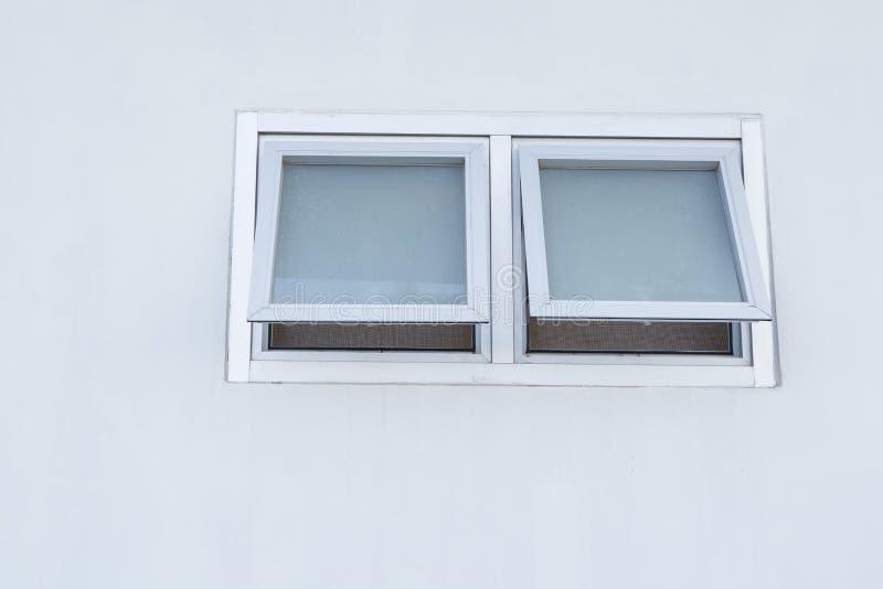 Μικρό παράθυρο γυαλιού αργιλίου στον τοίχο τσιμέντου στοκ φωτογραφία
