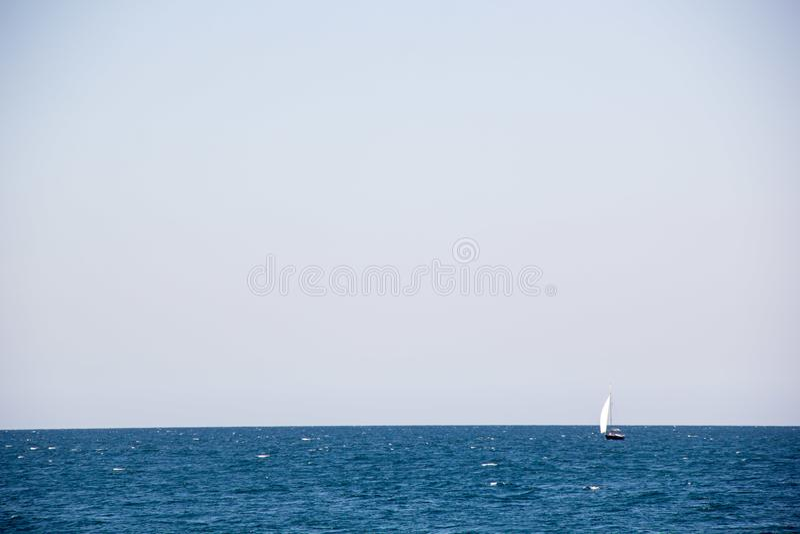 Μικρό πλέοντας γιοτ με τα μεγάλα άσπρα πανιά στην ανοικτή θάλασσα στον ορίζοντα στοκ εικόνα με δικαίωμα ελεύθερης χρήσης