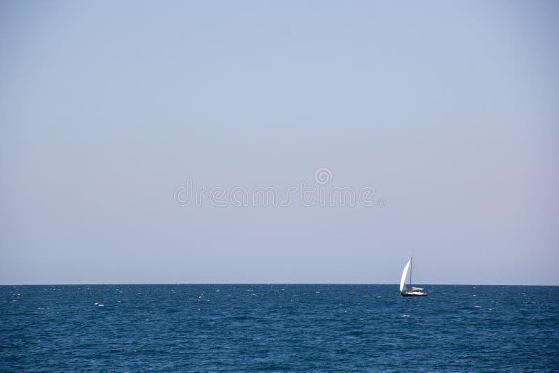 Μικρό πλέοντας γιοτ με τα μεγάλα άσπρα πανιά στην ανοικτή θάλασσα στον ορίζοντα στοκ φωτογραφίες με δικαίωμα ελεύθερης χρήσης