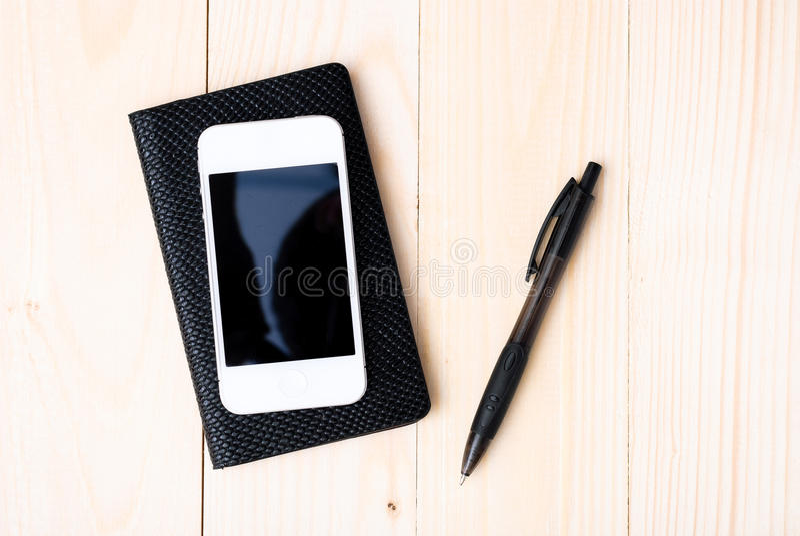 Μικρό σημειωματάριο με τη μάνδρα και το smartphone στοκ εικόνα με δικαίωμα ελεύθερης χρήσης