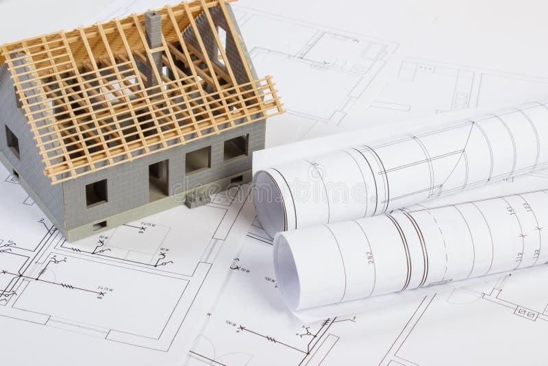 Μικρό σπίτι κάτω από την κατασκευή και ηλεκτρικά σχέδια, έννοια της οικοδόμησης του σπιτιού στοκ εικόνες