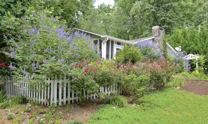 Μικρό σπίτι με έναν μεγάλο κήπο λουλουδιών στοκ εικόνες