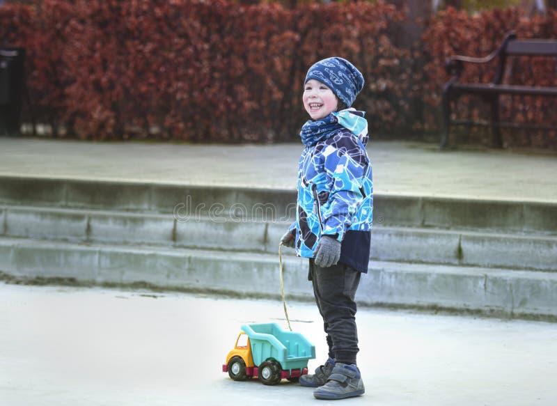 Μικρό χαμογελαστό αγόρι που κρατά ένα φορτηγό με παιχνίδια στοκ εικόνες