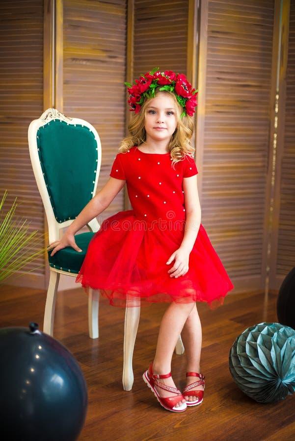 Μικρό χαμόγελο κοριτσιών, μόδα Παιδί που χαμογελά με το ξανθό hairstyle στο κόκκινο φόρεμα Έννοια σαλονιών ομορφιάς Haircare, κομ στοκ εικόνα