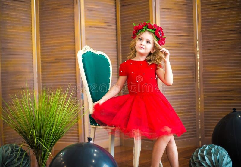 Μικρό χαμόγελο κοριτσιών, μόδα Παιδί που χαμογελά με το ξανθό hairstyle στο κόκκινο φόρεμα Έννοια σαλονιών ομορφιάς Haircare, κομ στοκ εικόνες