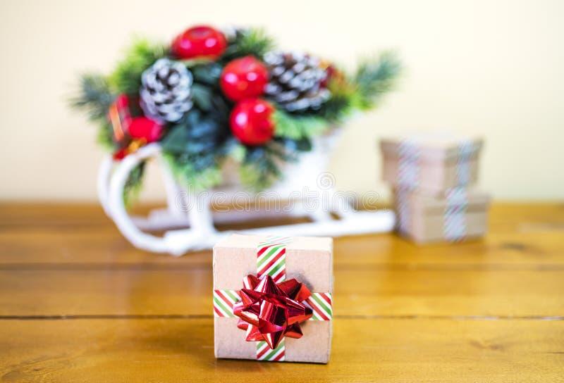Μικρό χαρτόνι giftbox που τυλίγεται στη ριγωτή κορδέλλα και το λαμπρό holi στοκ φωτογραφίες