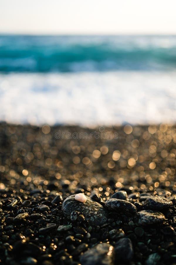 Μικρό χαλίκι στη μαύρη παραλία με το όμορφο βράδυ ελαφρύ με το ιδανικό υπόβαθρο bokeh στοκ φωτογραφία με δικαίωμα ελεύθερης χρήσης
