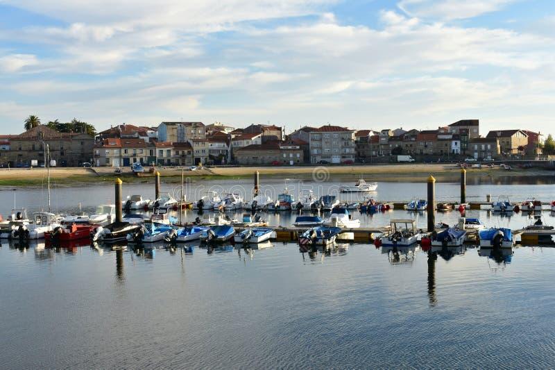 Μικρό ψαροχώρι με την αποβάθρα και τις βάρκες Παραλία, λιμάνι και περίπατος με τα δέντρα Φως ηλιοβασιλέματος, μπλε ουρανός με τα  στοκ φωτογραφίες