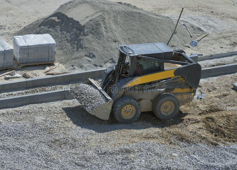 Μικρό breakstone κίνησης εκσακαφέων φορτωτών στην περιοχή κατασκευής στοκ φωτογραφία με δικαίωμα ελεύθερης χρήσης