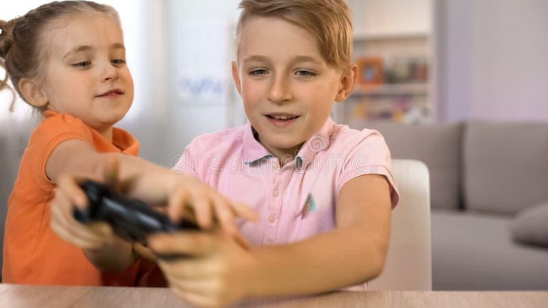 Μικρών κοριτσιών ενοχλητικό παιχνίδι κονσολών αδελφών παίζοντας, παιδιά που παλεύει το πηδάλιο στοκ φωτογραφίες
