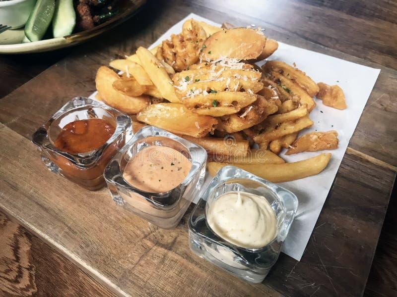 Μικτές τσιπ ή πατάτες τηγανητών με τη βύθιση της σάλτσας στοκ εικόνα