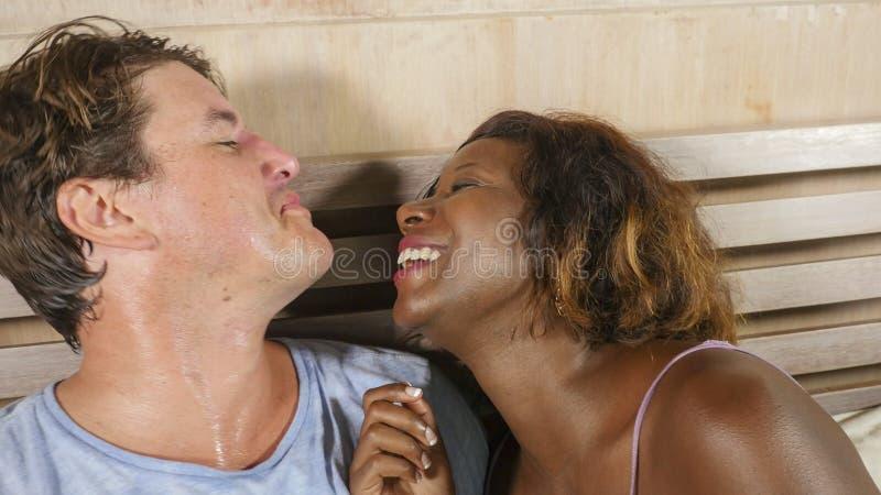 Μικτή ερωτευμένη αγκαλιά ζευγών έθνους μαζί στο σπίτι στο κρεβάτι με την όμορφη εύθυμη μαύρη αμερικανική φίλη ή τη σύζυγο afro κα στοκ εικόνες με δικαίωμα ελεύθερης χρήσης