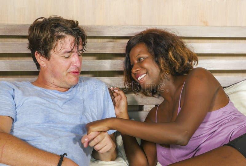 Μικτή ερωτευμένη αγκαλιά ζευγών έθνους μαζί στο σπίτι στο κρεβάτι με την όμορφη εύθυμη μαύρη αμερικανική φίλη ή τη σύζυγο afro κα στοκ εικόνα