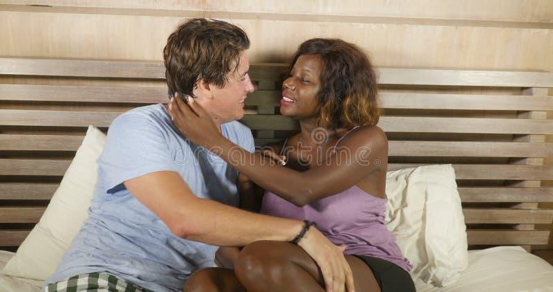 Μικτή ερωτευμένη αγκαλιά ζευγών έθνους μαζί στο σπίτι στο κρεβάτι με την όμορφη εύθυμη μαύρη αμερικανική φίλη ή τη σύζυγο afro κα στοκ φωτογραφίες