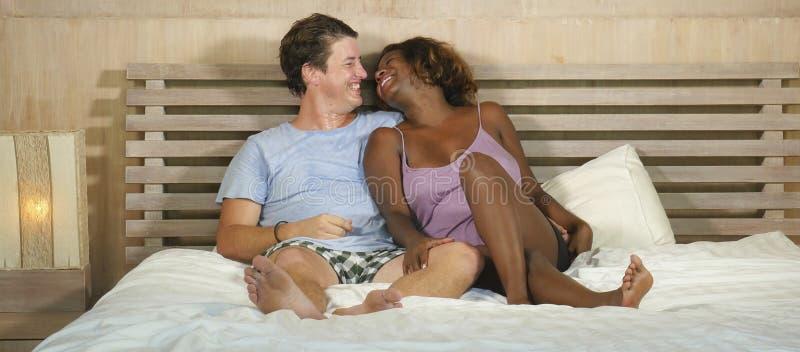 Μικτή ερωτευμένη αγκαλιά ζευγών έθνους μαζί στο σπίτι στο κρεβάτι με την όμορφη εύθυμη μαύρη αμερικανική φίλη ή τη σύζυγο afro κα στοκ εικόνα με δικαίωμα ελεύθερης χρήσης