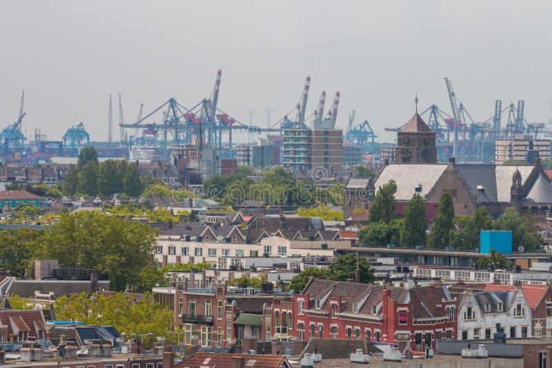 Μικτή κλασική αρχιτεκτονική των φυλλωδών αστικών πολυκατοικιών του Ρότερνταμ στο πρώτο πλάνο με τους γερανούς λιμένων λιμενικών π στοκ εικόνα