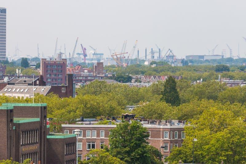 Μικτή κλασική αρχιτεκτονική των φυλλωδών αστικών πολυκατοικιών του Ρότερνταμ στο πρώτο πλάνο με τους γερανούς λιμένων λιμενικών π στοκ φωτογραφίες