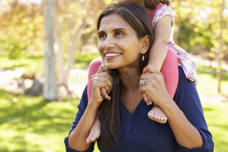 Μικτή μητέρα φυλών που φέρνει τη νέα κόρη στους ώμους, συγκομιδή στοκ φωτογραφία με δικαίωμα ελεύθερης χρήσης