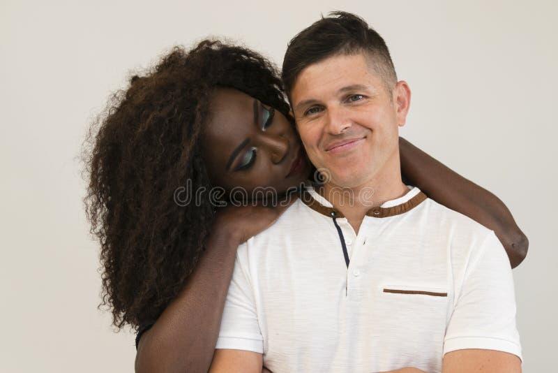 Μικτή οικογένεια φυλών Νέα τρυφερή σύζυγος που αγκαλιάζει το σύζυγό του αγάπη στοκ εικόνα
