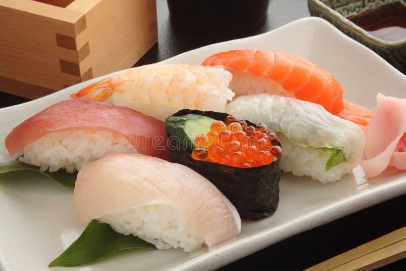 Μικτή πιατέλα σουσιών στο άσπρο πιάτο με τη χάρη, ιαπωνικά τρόφιμα στοκ εικόνες
