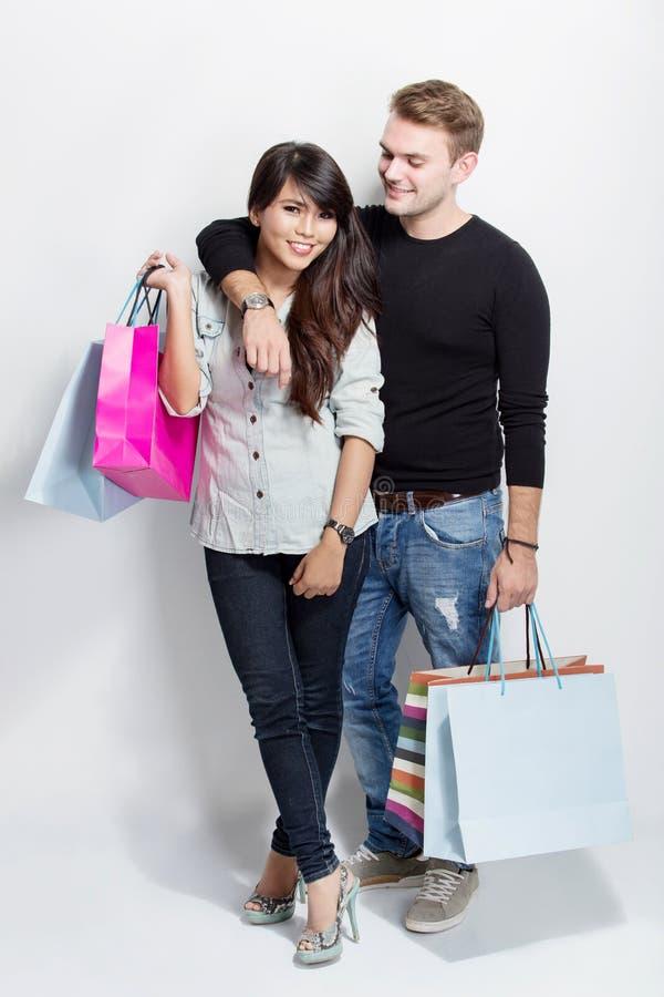 Μικτή τσάντα αγορών εκμετάλλευσης ζευγών μόνιμη στο άσπρο υπόβαθρο στοκ φωτογραφίες με δικαίωμα ελεύθερης χρήσης