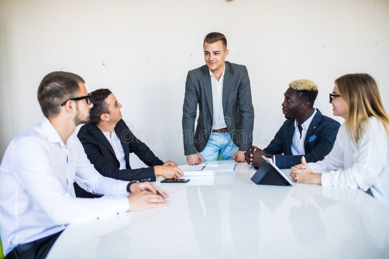 Μικτοί επιχειρηματίες φυλών που κάθονται και που συναντιούνται και συζήτηση στην παρουσίαση ηγετών αιθουσών και προσωπικό γραφείο στοκ φωτογραφία