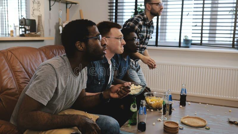 Μικτός αθλητισμός ρολογιών υποστηρικτών φυλών ανδρικός στη TV 4K Οι θαυμαστές γιορτάζουν τη νίκη στόχου που κρατά το βρετανικό μα στοκ φωτογραφία