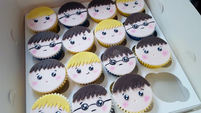 Μικτό κιβώτιο του προσώπου αγοριών cupcakes στοκ φωτογραφίες