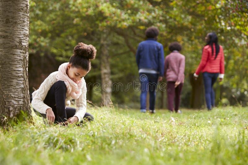 Μικτό κορίτσι φυλών που γονατίζει στο πάρκο για να δέσει το παπούτσι της, η οικογένειά της που περπατά στο υπόβαθρο, χαμηλή γωνία στοκ φωτογραφία με δικαίωμα ελεύθερης χρήσης