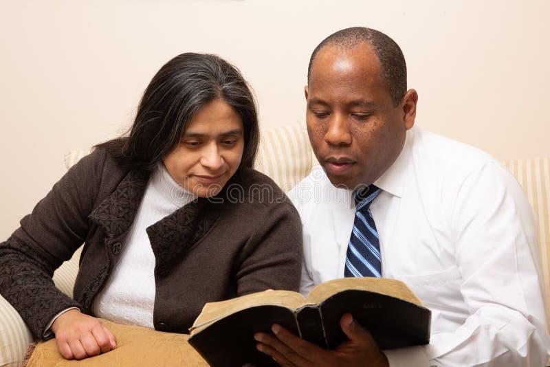 Μικτό συναγωνισμένο χριστιανικό ζεύγος που μελετά τη Βίβλο από κοινού στοκ εικόνες