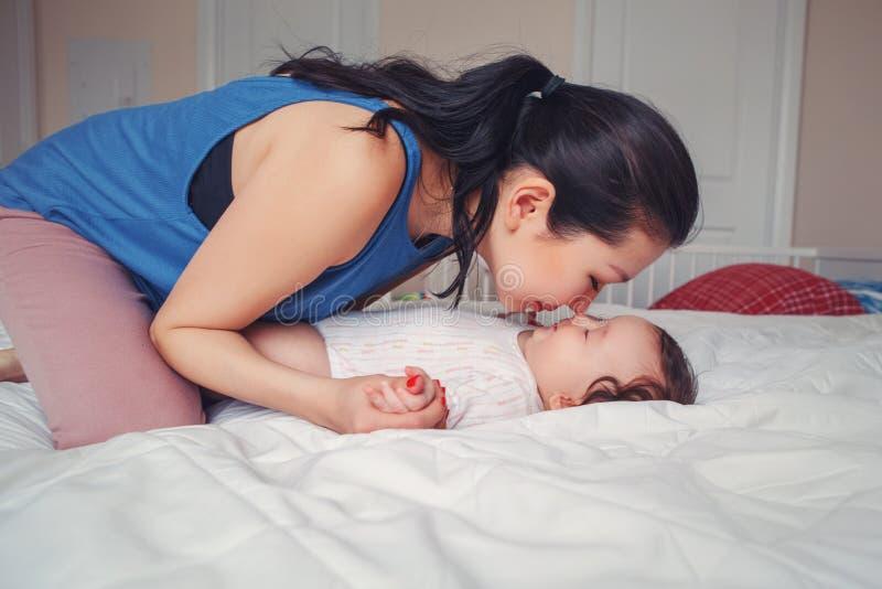 Μικτό φίλημα μητέρων φυλών ασιατικό σχετικά με το αγκάλιασμα του νεογέννητου μωρού νηπίων της στοκ εικόνες