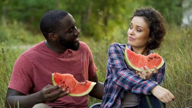 Μικτό Flirty ζεύγος που συζητά τα σχέδια για το μέλλον, που τρώει το εύγευστο καρπούζι στοκ εικόνες με δικαίωμα ελεύθερης χρήσης