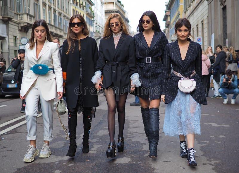 ΜΙΛΑΝΟ - 24 ΦΕΒΡΟΥΑΡΊΟΥ 2018: Πέντε bloggers μόδας που περπατούν για τους φωτογράφους στην οδό μετά από τη επίδειξη μόδας ERMANNO στοκ εικόνα