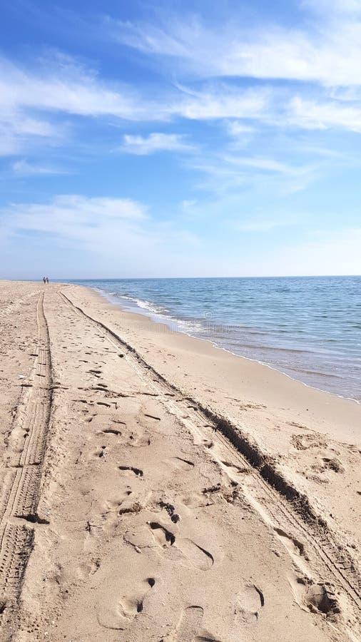 Μινιμαλιστικό τοπίο παραλιών θάλασσας με διαδρομές ροδών αυτοκινήτων στην άμμο και δύο σκιαγραφίες ανθρώπων στον ορίζοντα στοκ φωτογραφίες με δικαίωμα ελεύθερης χρήσης