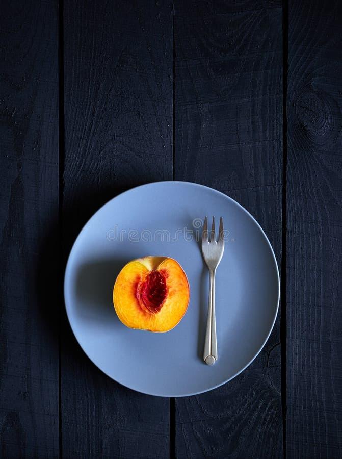 Μισά ροδάκινο και δίκρανο στο πιάτο στοκ εικόνες