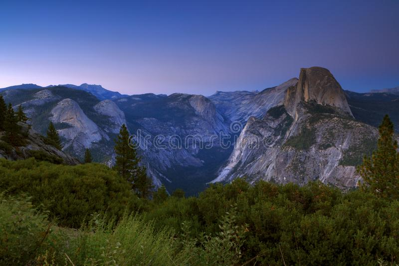 Μισές σύνοδοι κορυφής αναρρίχησης βράχου θόλων στο όμορφο χρυσό φως στο SU στοκ εικόνες