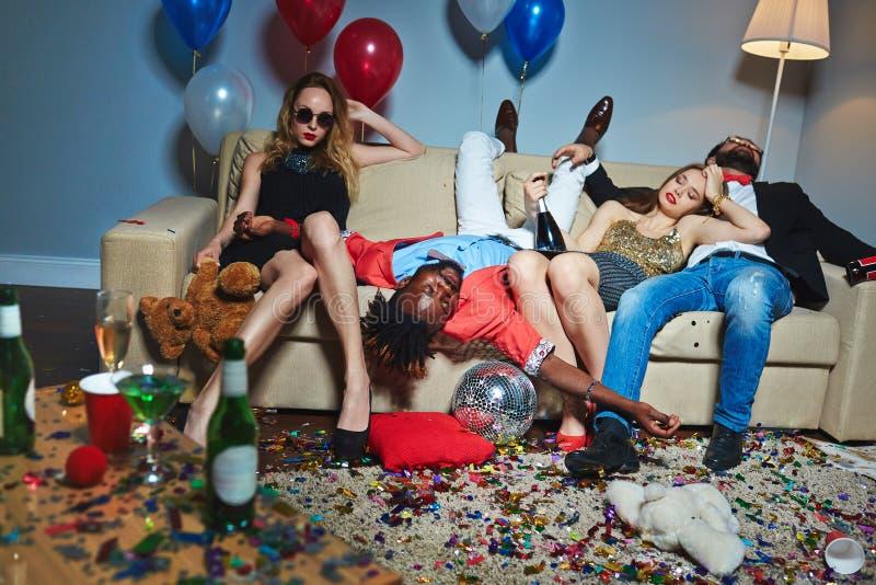 Μισομεθυσμένοι φίλοι στο ακατάστατο καθιστικό στοκ φωτογραφία με δικαίωμα ελεύθερης χρήσης
