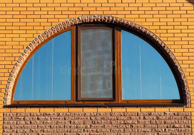 Μισοστρόγγυλο παράθυρο στο τουβλότοιχο, εξωτερικό σπιτιών, κινηματογράφηση σε πρώτο πλάνο στοκ εικόνα