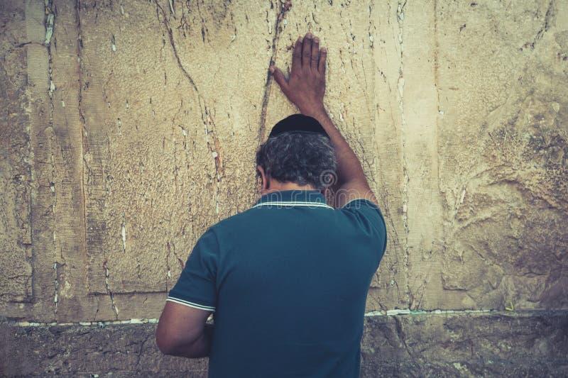 Μισό-μήκος που πυροβολείται ενός ηληκιωμένου που στέκεται με το χέρι του επάνω και σχετικά με τον εβραϊκό wailing τοίχο Προσκύνημ στοκ εικόνα