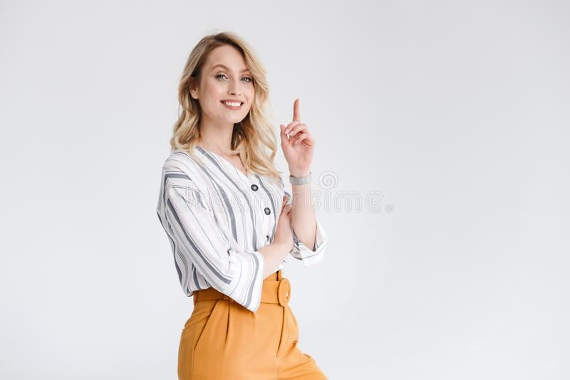 Μισό πορτρέτο στροφής της νέας γυναίκας που φορά τα περιστασιακά ενδύματα που χαμογελούν στη κάμερα και που δείχνουν το δάχτυλο π στοκ φωτογραφία με δικαίωμα ελεύθερης χρήσης