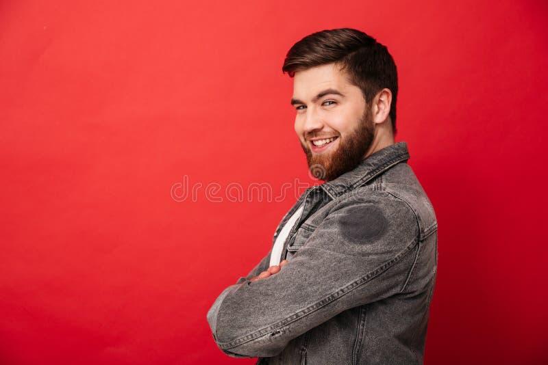 Μισό πορτρέτο στροφής του ελκυστικού ατόμου στην τοποθέτηση σακακιών τζιν στο γ στοκ εικόνα με δικαίωμα ελεύθερης χρήσης