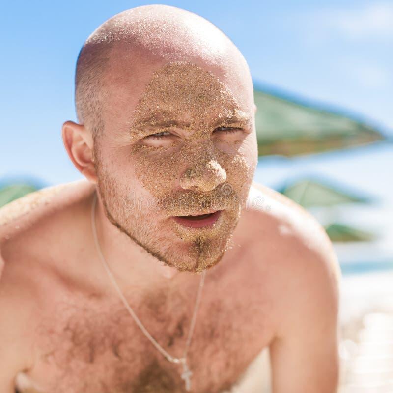 Μισό πρόσωπο ενός όμορφου ατόμου που καλύπτεται με την άμμο στοκ εικόνες