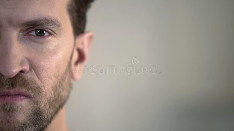 Μισό πρόσωπο του επιθετικού ατόμου που κοιτάζει με την έχθρα στη κάμερα, εσωτερικός τύραννος στοκ φωτογραφία με δικαίωμα ελεύθερης χρήσης