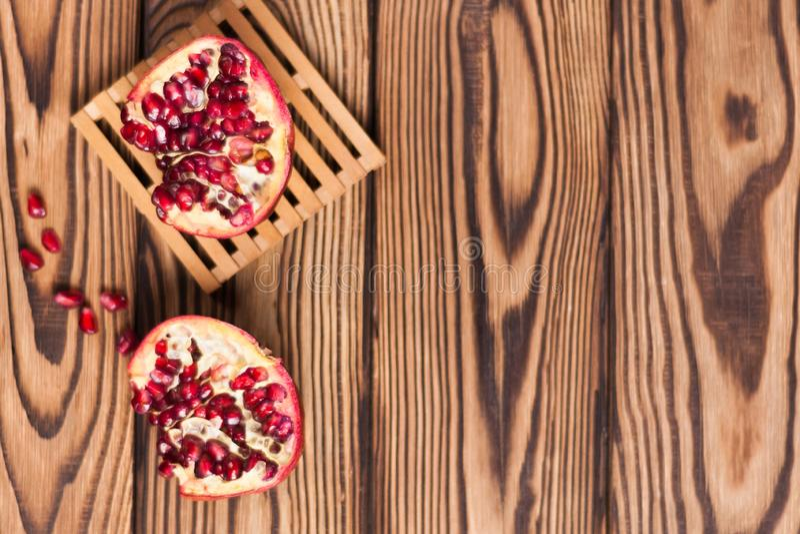 Μισό του κόκκινου φρέσκου ώριμου ροδιού με τους σπόρους στην παλέτα εκτός από το ένα κομμάτι του ροδιού και των διεσπαρμένων σπόρ στοκ φωτογραφία με δικαίωμα ελεύθερης χρήσης
