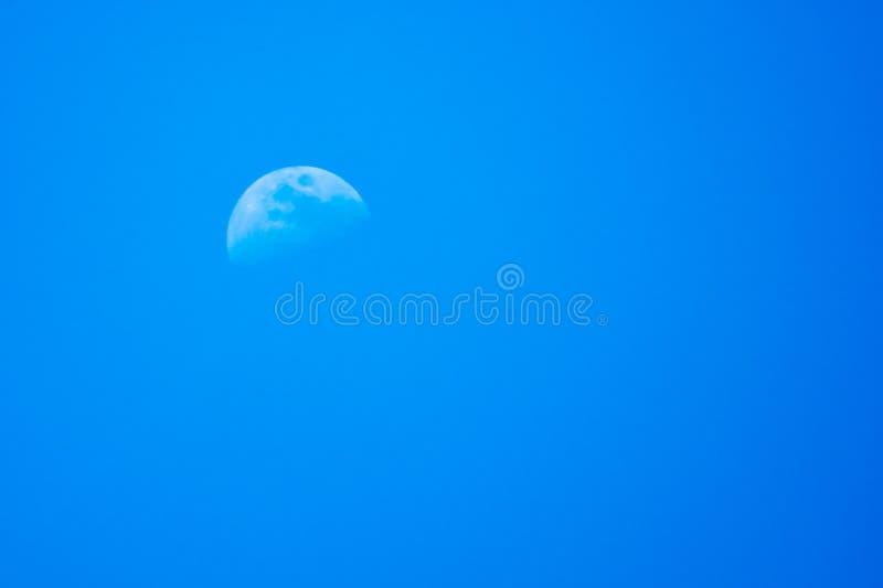 Μισό φεγγάρι στον μπλε νυχτερινό ουρανό στοκ φωτογραφίες