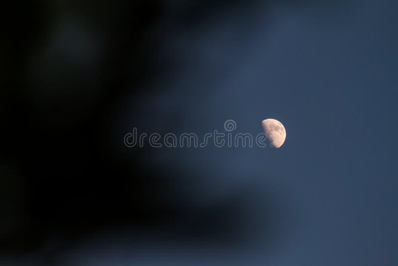 Μισό φεγγάρι στο μπλε ουρανού, και σύννεφα του Μαύρου ως υπόβαθρο στοκ εικόνες